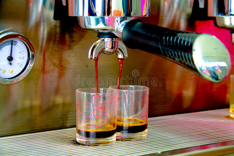 Coffee machine brewing a coffee. Coffee pouring into shot glasse royalty free stock photo