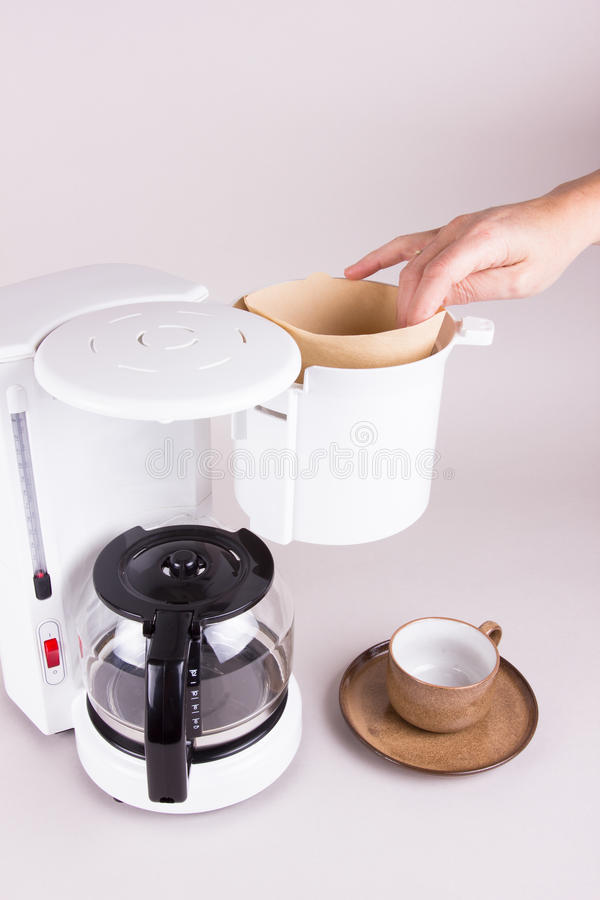 Coffee machine with filter bag and cup. Employing a filter bag in the coffee maker with hand royalty free stock photo