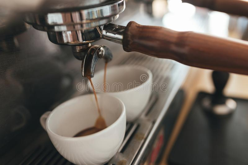 Coffee machine making coffee and pouring into white cups in coffee shop stock photography