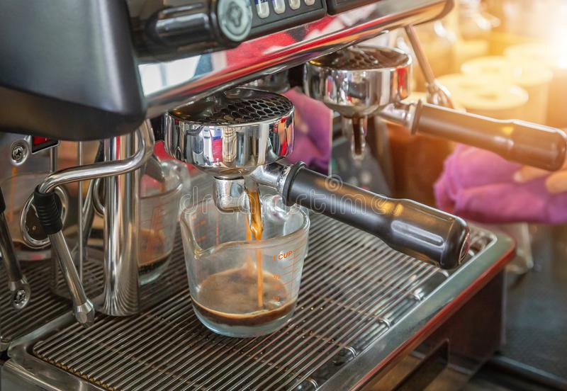 Coffee machine preparing fresh coffee and pouring into cup. Close up coffee machine preparing fresh coffee and pouring into cup at coffee shop royalty free stock photo