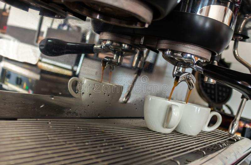 Coffee machine serving two white cups with reflections, steam and water drops stock photo