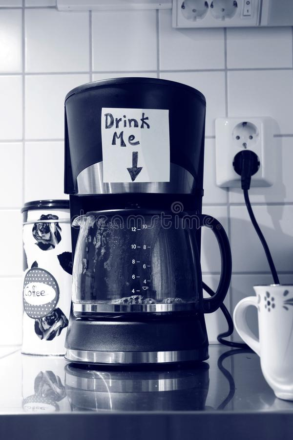 A coffee machine in working mode has a written note stuck on it above the carafe saying `Drink me` with an arrow pointing down at. Coffee machine in working mode royalty free stock photography