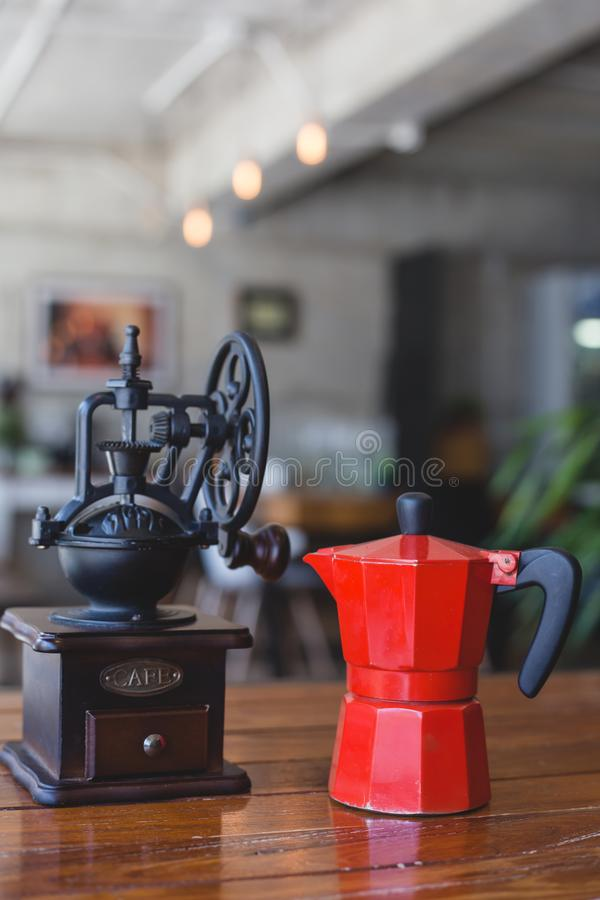 Coffee maker. ` moka pot ` with manaul coffee grinder on table in coffee shop stock images