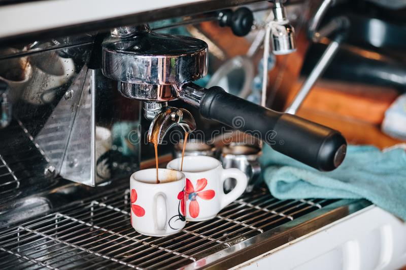 Coffee Maker making coffee flowing in cup stock photo