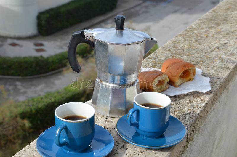 Coffee maker moka pot with roasted coffee beans. Space for text, horizontal. Breakfast concept. Pot and two blue cups of. Coffee maker moka pot and with roasted stock photography