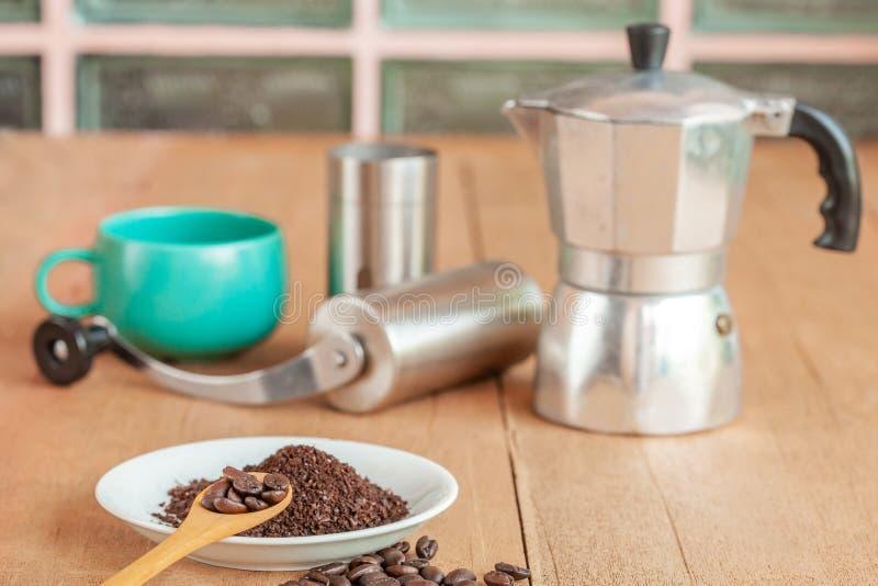 Coffee maker tool and moka pot on wood. Table royalty free stock photos