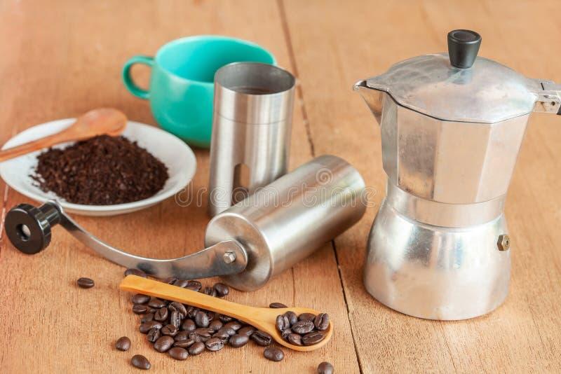Coffee maker tool and moka pot on wood. Table royalty free stock image