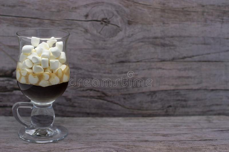 Coffee And Many Small Marshmallows In A Transparent Glass Cup On A Wooden Background. The Photo In Cold Colors royalty free stock photography