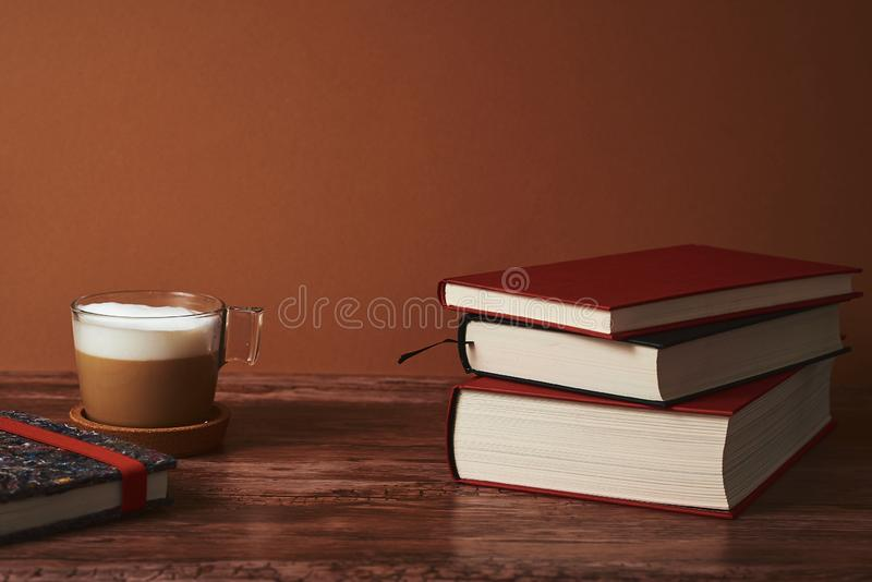 Coffee with milk and books on a brown wooden table. royalty free stock photos
