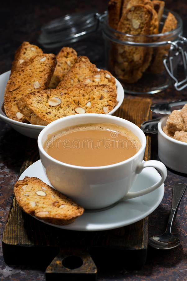 Coffee with milk and Italian cookies cantucci, vertical closeup. Coffee with milk and Italian cookies cantucci, closeup stock photos
