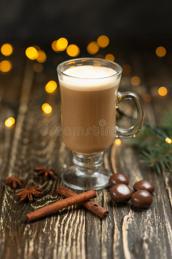 Coffee with milk, latte with cinnamon sticks and anise stars and sweets, Christmas tree on a wooden background, with lights from a stock photography