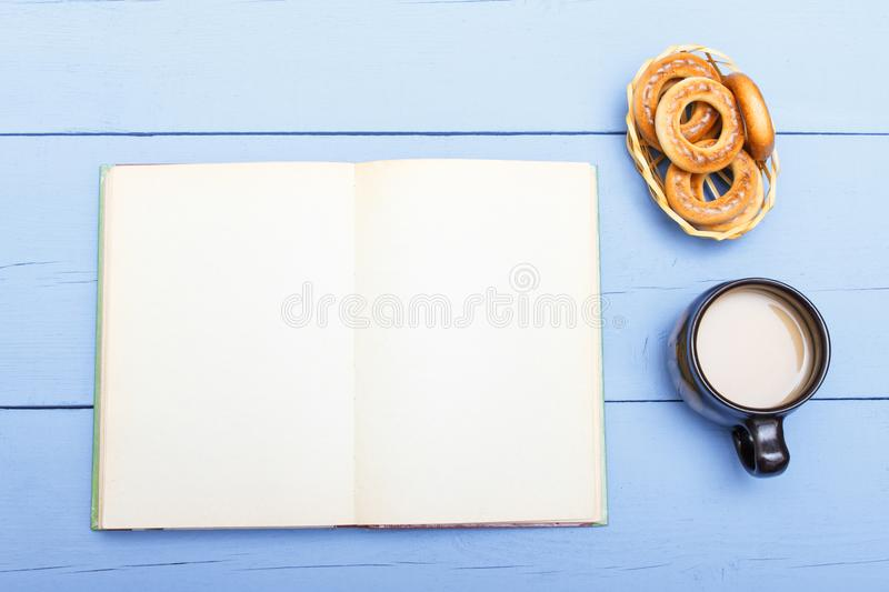 Coffee with milk and open book with empty page on wooden table. Light breakfast and education royalty free stock images