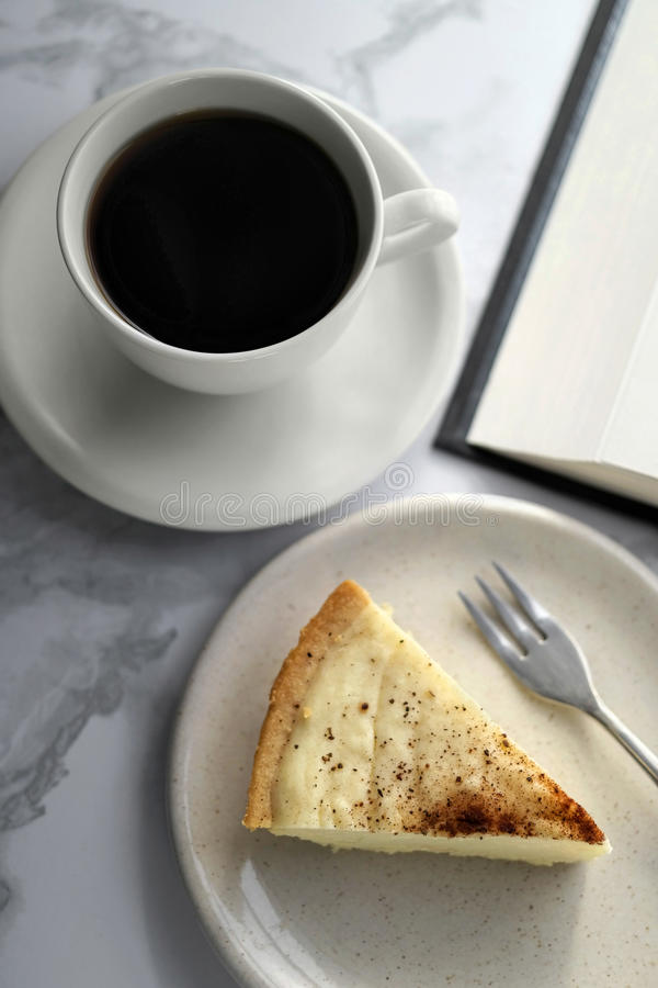 Coffee and Milk Tart. Photo of black coffee with slice of Milk Tart and a book in the background stock photo