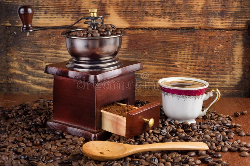 Coffee mill grinder and cup of coffee and wooden spoon on old retro background with roasted beans stock images