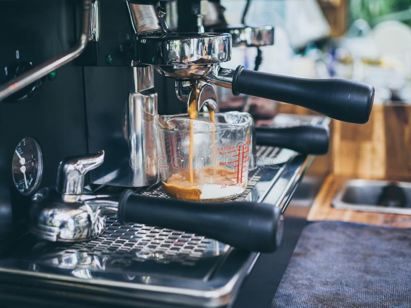 Coffee mixed with milk flowing in beaker mug with portafilter on coffee machine royalty free stock images