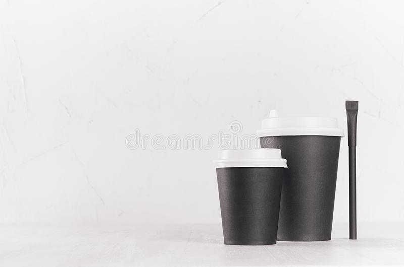 Coffee mockup - big and small black paper cups with white caps and sugar bag on white wood table with copy space, coffee shop. Coffee mockup - big and small stock images