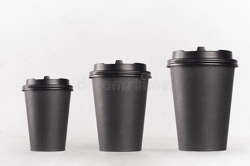 Coffee mockup - set of three different size blank black paper cups with cap on white wood table, coffee shop interior. royalty free stock image