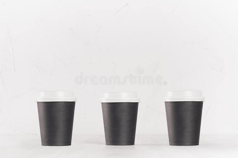 Coffee mockup - set of three small blank black paper cups with white cap on white wood table, coffee shop interior. Modern elegant concept for branding stock photos