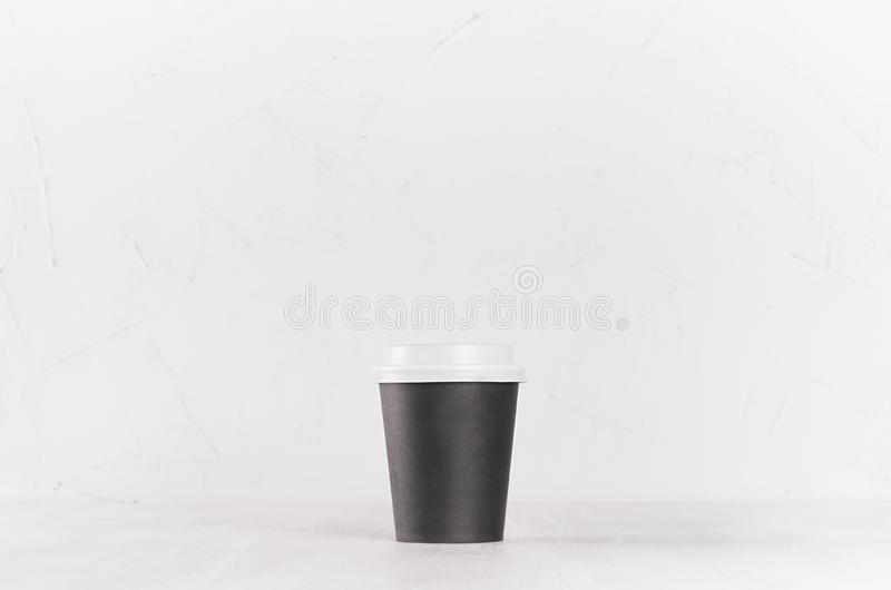 Coffee mockup - small blank black paper cup with white cap on white wood table, coffee shop interior. stock photo