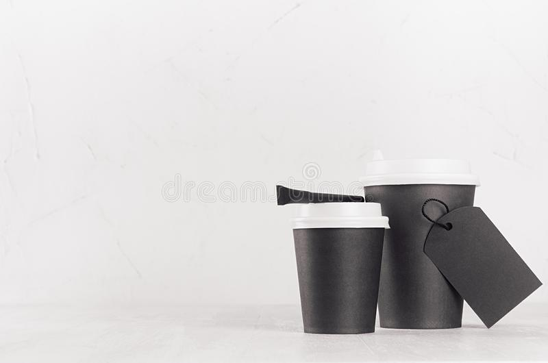 Coffee mockup - two black paper cups with white caps, blank label and sugar bag on white wood table with copy space, coffee shop. royalty free stock image