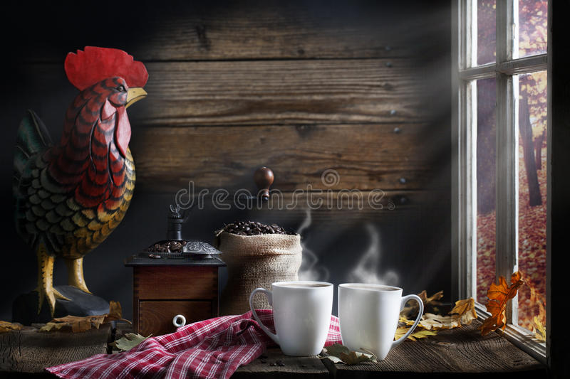 Coffee Morning Light. Two steaming cups of coffee on wood table with vintage coffee grinder, burlap bag of whole beans and carved wood rooster in background stock image