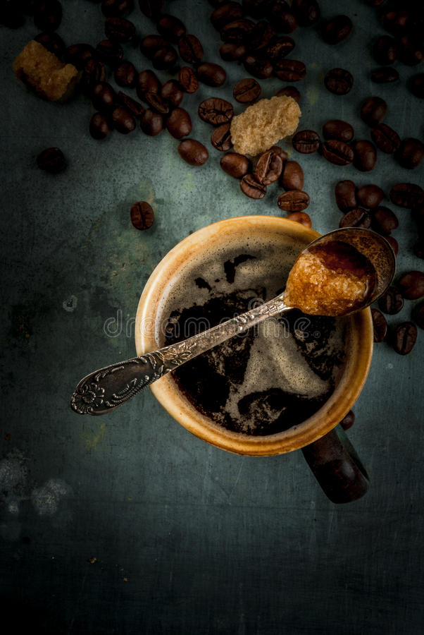 Coffee mug with beans and sugar. Coffee cup with beans and sugar on vintage metal background, copy space, top view royalty free stock photography