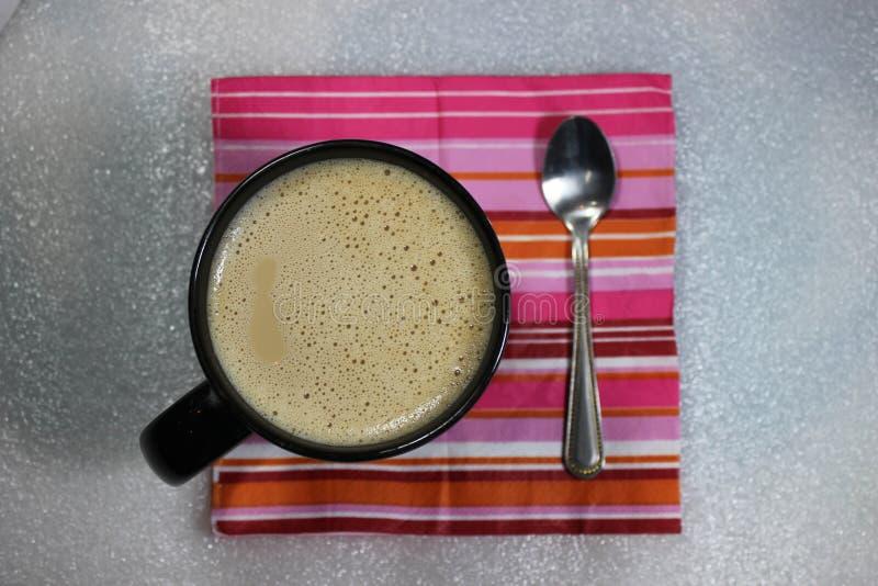 Coffee mug on colorful napkin royalty free stock image