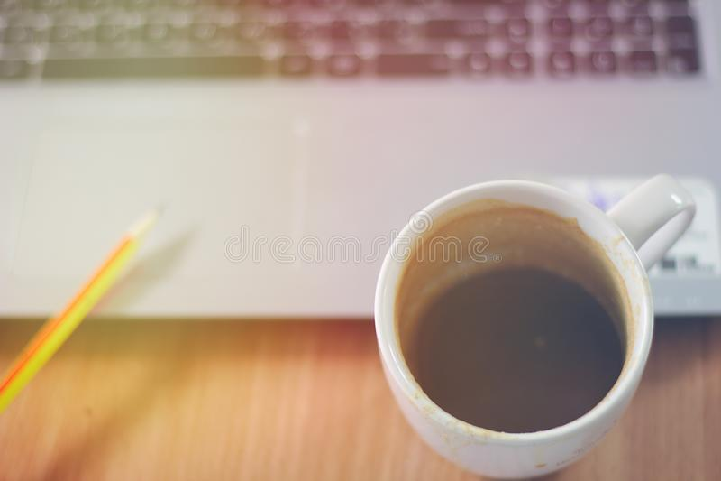 Coffee mug on the desk With a notebook computer, a pencil, a wooden table top with bright morning sunlight stock image