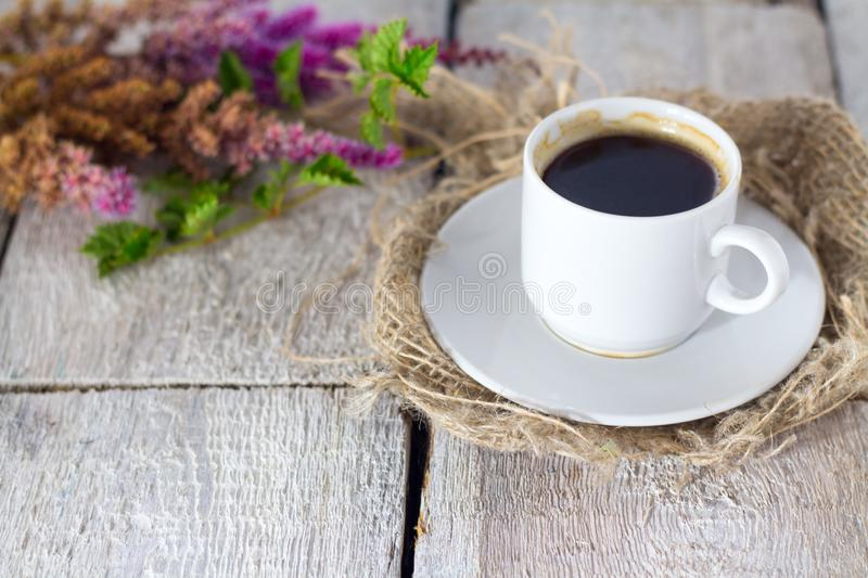 Coffee mug with flowers good morning on white rustic table. stock photo