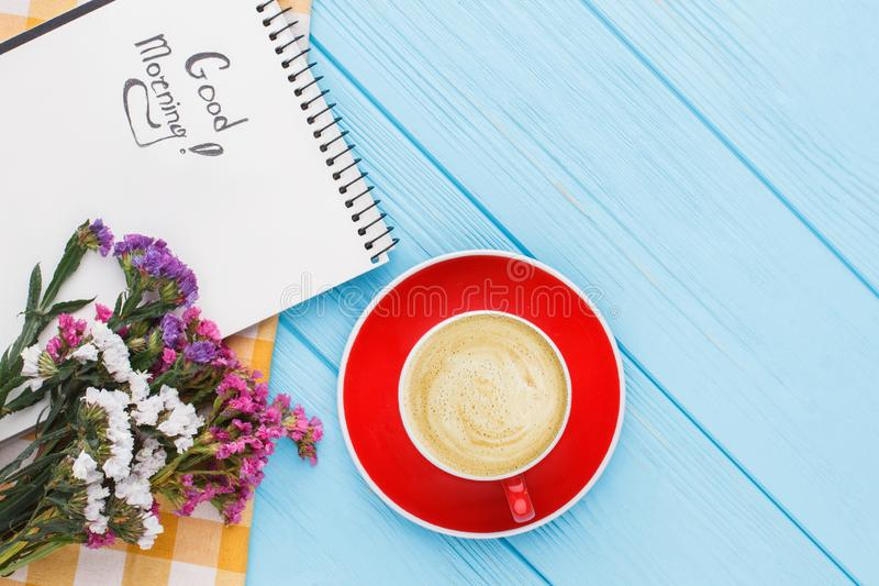 Coffee mug with flowers and notepad with good morning wish. Top view. Blue wooden table background royalty free stock photography