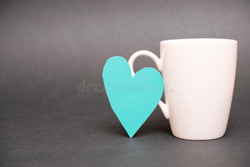 Coffee mug love. Real cut out of paper heart leaning on a coffee mug for your romantic, coffee addiction or effects of coffee drinking on the heart concepts stock images