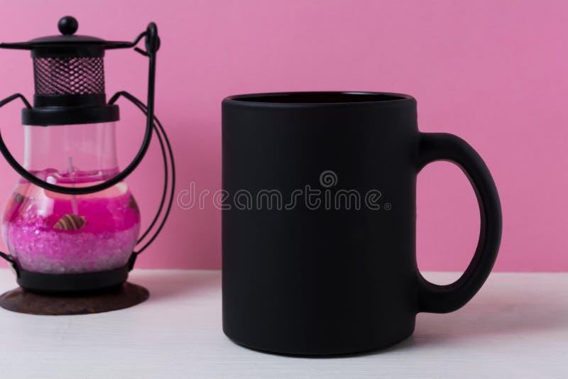 Coffee mug mockup with black metal candle lantern. Black coffee mug mockup with metal candle lantern on the pink background. Empty mug mock up for brand stock photos