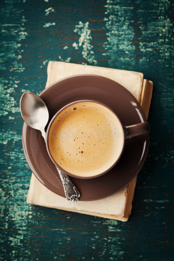 Coffee mug with old book on teal rustic table, cozy breakfast, vintage style, above stock photography
