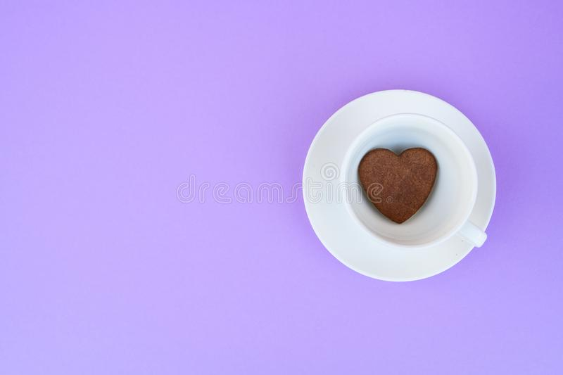 Coffee mug on a purple background. background Breakfast, drinks and cafe menu concept - coffee cup on purple background, toplay. Flatlay. cookies to coffee stock photo