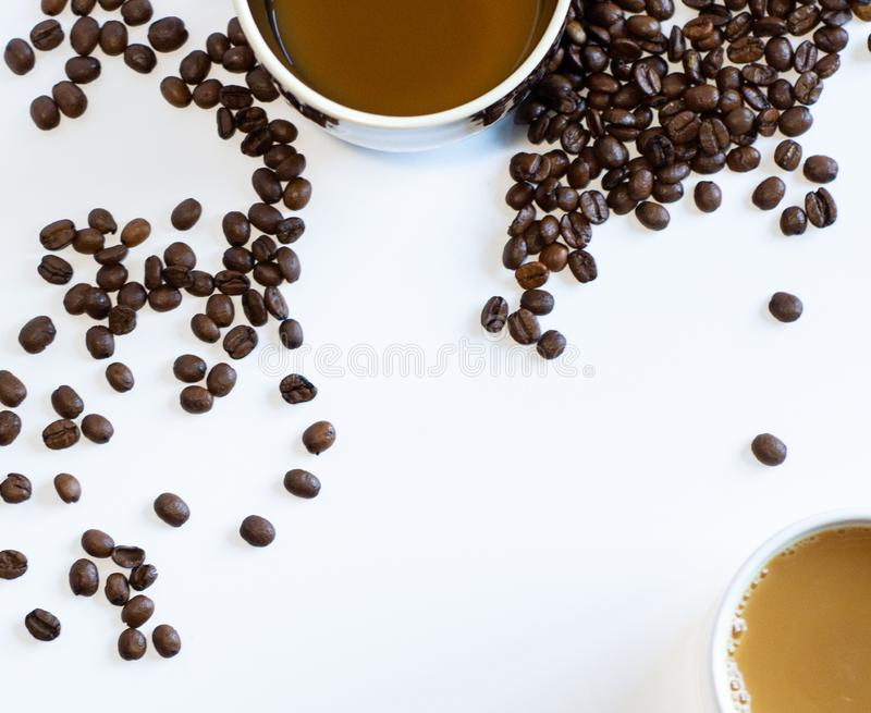 Aerial view of coffe mugs with coffee beans on white background with copy space royalty free stock image