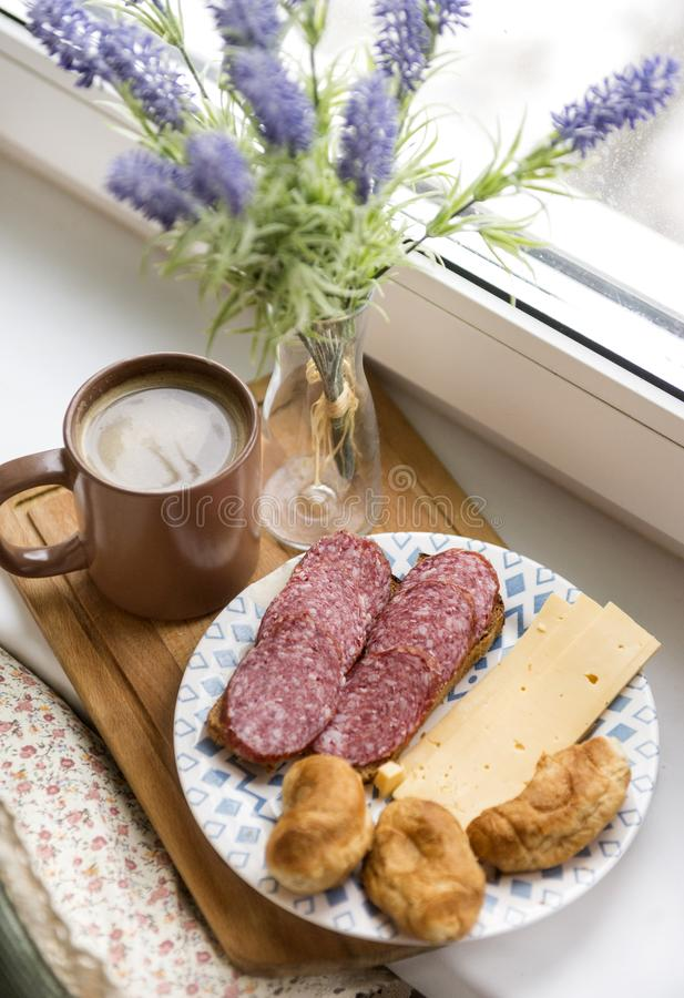 Coffee mug, sandwich with salami, pieces of cheese, mini croissants, lavender flowers in a vase stock photo
