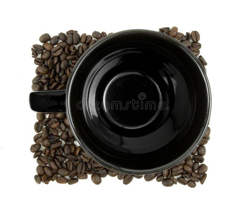 Coffee mug sitting in beans stock photos