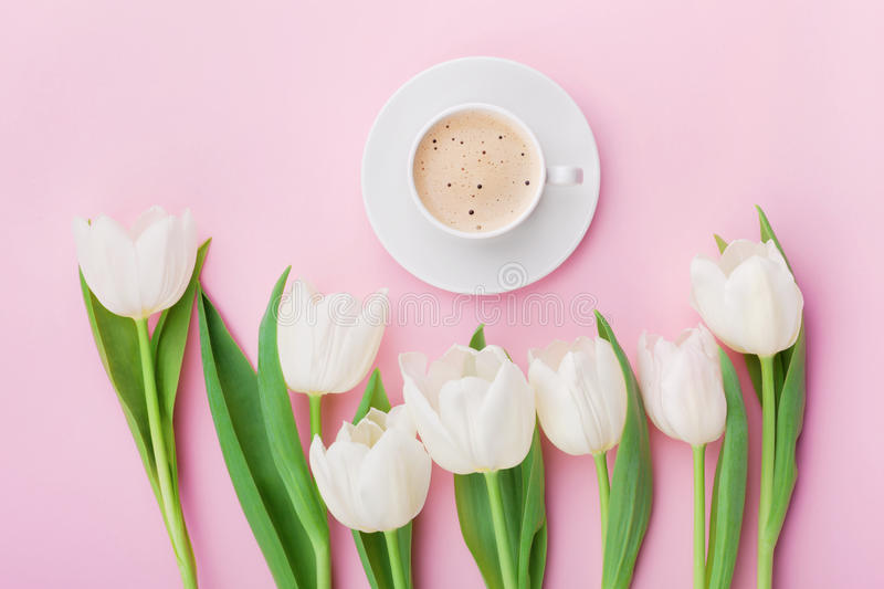Coffee mug with spring tulip flowers for good morning on pink table above in flat lay style. Breakfast on Mothers or Womens day. Coffee mug with spring tulip royalty free stock image