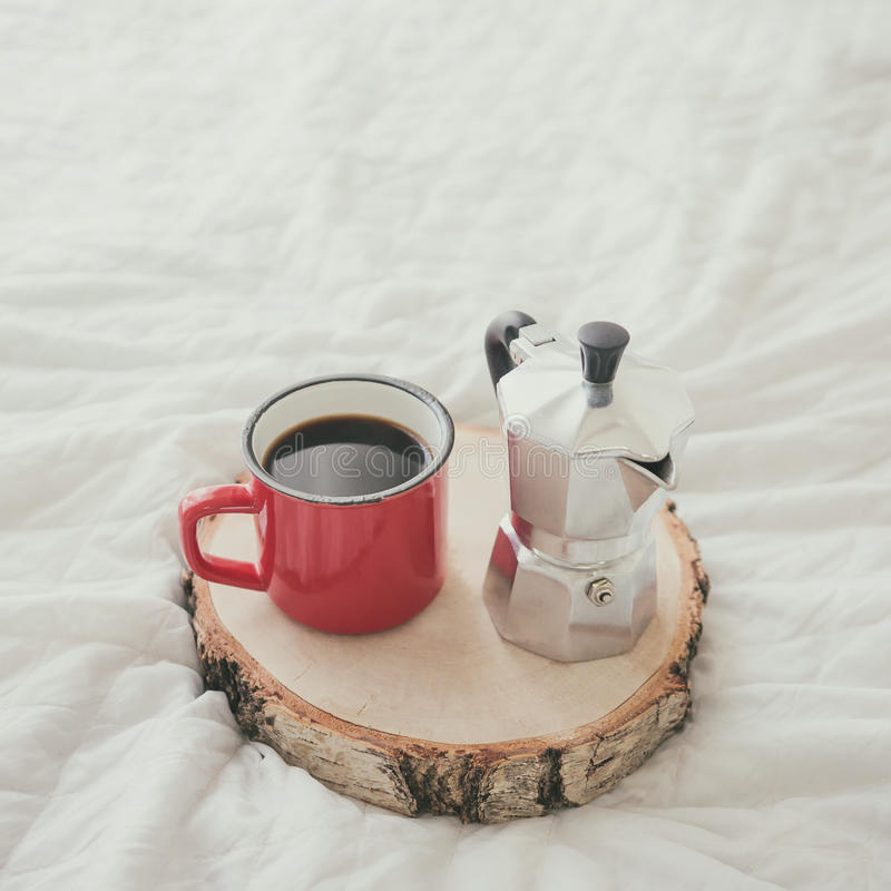 Coffee mug with steel coffee maker on wooden tray on white bed sheet. Close-up of coffee mug with steel coffee maker on wooden tray on white bed sheet stock photos