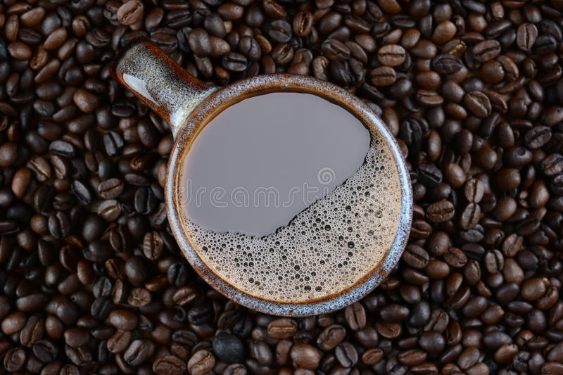 Coffee Mug Surrounded by Fresh Roasted Beans. High angle shot of a coffee mug surrounded by fresh roasted beans stock photography