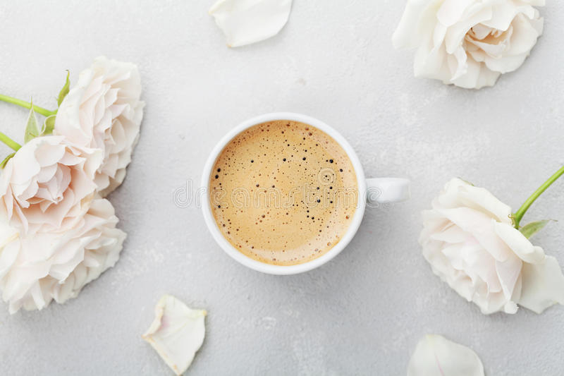 Coffee mug and vintage rose flowers for good morning on gray stone table from above in flat lay style. Beautiful breakfast. Coffee mug and vintage rose flowers royalty free stock images