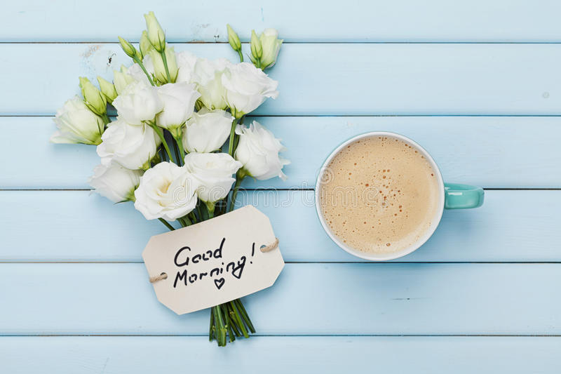 Coffee mug with white flowers and notes good morning on blue rustic table from above. Beautiful breakfast. Flat lay. Coffee mug with white flowers and notes royalty free stock photography