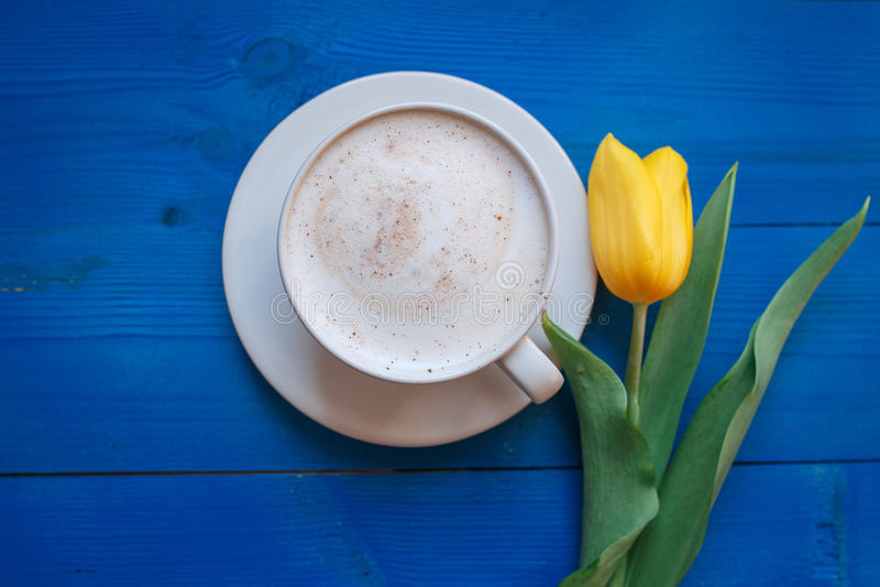Coffee mug with yellow tulip flowers royalty free stock image