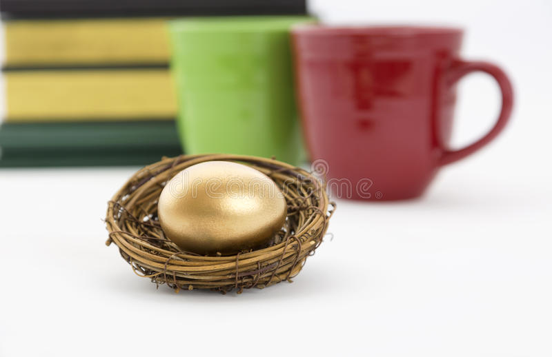 Coffee mugs, books, and gold nest egg. Successful, collaborative investment reflected in two coffee mugs, red and green, and books combined with selective focus royalty free stock photo