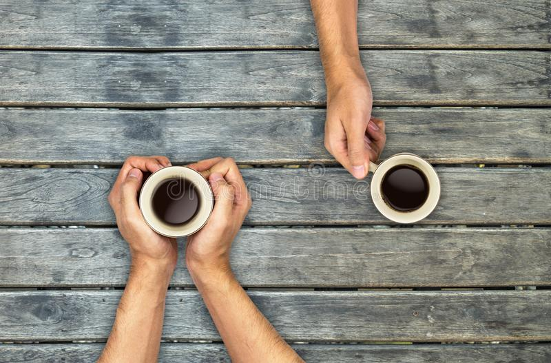 Coffee mugs hands holding on wood table stock images