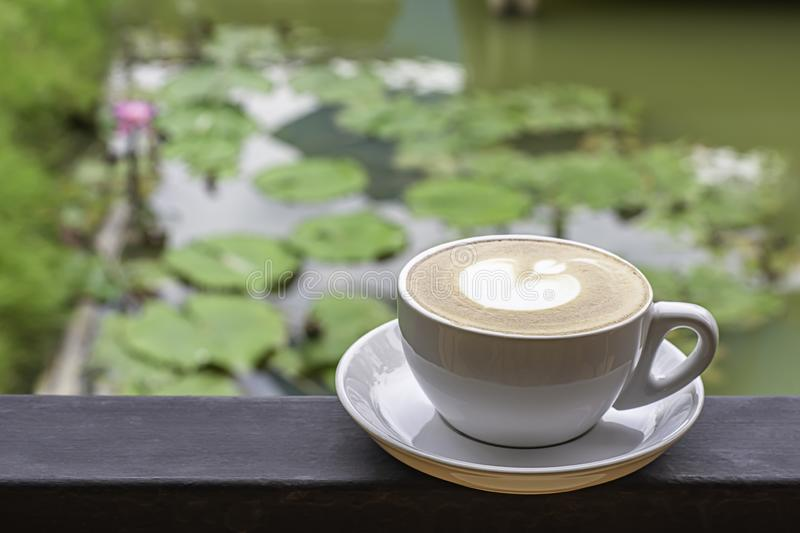 Coffee Mugs white plate with The heart shaped makeup on  iron balconies  Background Lotus pond.  royalty free stock image