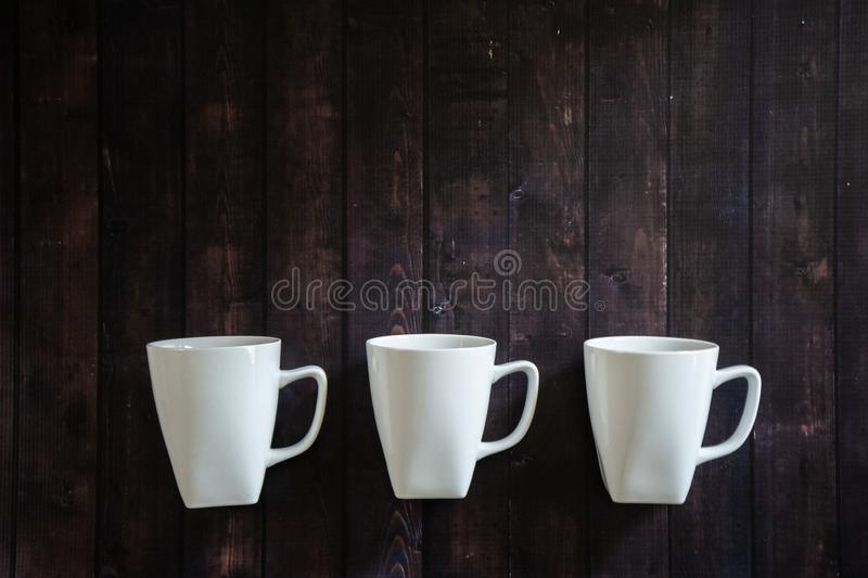 3 coffee mugs on a wooden table background - morning pick me up drink stock images