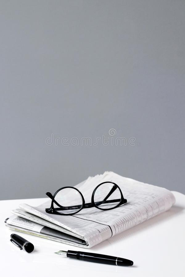 Glasses on a newspaper with a pen business stock image