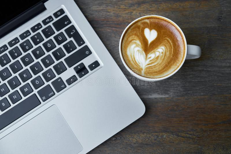 Coffee next to laptop computer royalty free stock photos
