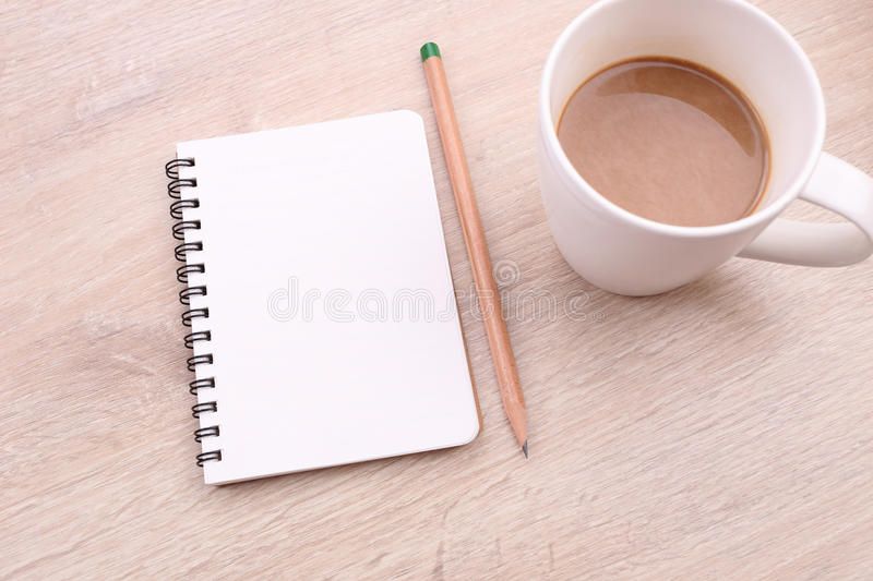 Coffee with note book and pencil on wooden background royalty free stock photo